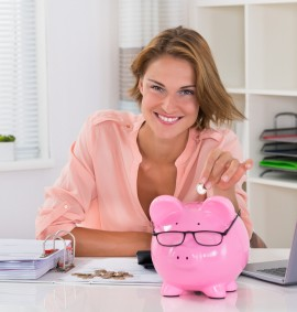 Happy Woman With Bills Putting Coin In Piggybank At Desk